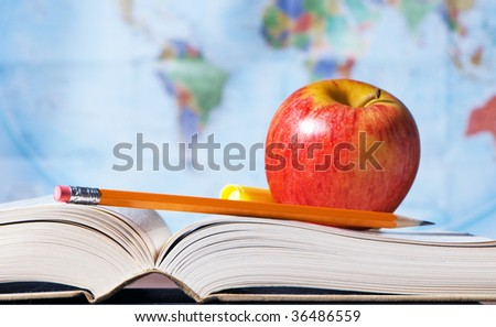 Book and pencil with world map background, focus on book binding