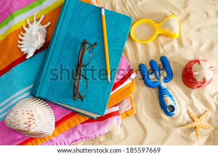 Book and reading glasses on a colorful beach towel on a sandy beach with kids plastic toys, a starfish and seashells conceptual of a tropical summer vacation