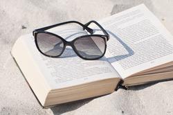 Book and sunglasses on a sand beach