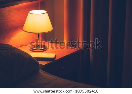 Book and vintage lamp on night table in hotel room. Retro styled bedroom interior. #1095582410