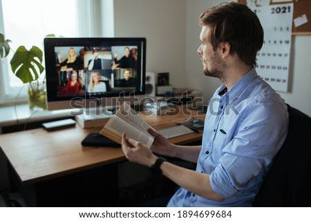 Book Club Online. Handsome young man in casual clothes reading a book in a video conference call  Boring group video chat  While Practicing Social Distancing. Online education video conferencing