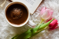 Book, coffee and tulips on a white furry carpet