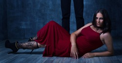 Book cover concept. Love couple Dominance and submission. Woman lay on the floor in red dress with hose