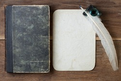 Book cover, quill and inkwell, old grunge paper on wood background