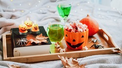 Book, halloween decor, candles, popcorn and drinks on tray on bed, halloween reading concept with bokeh background
