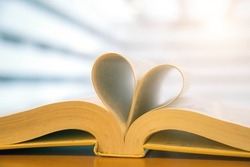Book  in heart shape on desk at library for reading education learning or lifestyle love to read and february valentine day concepts.