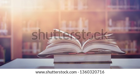 Book in library with old open textbook, stack piles of literature text archive on reading desk, and aisle of bookshelves in school study class room background for academic education learning concept