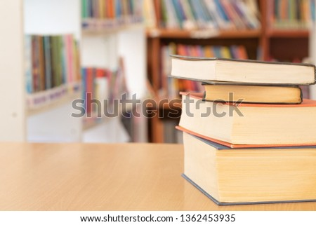 Book in library with old open textbook, stack piles of literature text archive on reading desk, and aisle of bookshelves in school study class room background for academic education learning concept  #1362453935