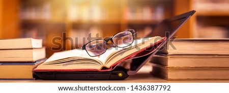 Book in library with old open textbook, stack piles of literature text archive on reading desk, and aisle of bookshelves in school study class room background for academic education learning concept #1436387792