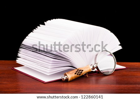 book of justice and magnifying glass on wooden table and black background