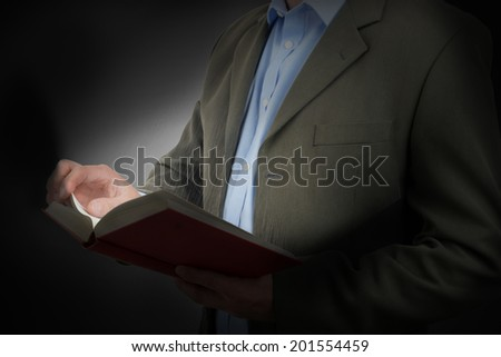 book of knowledge see the light, a man in a suit reading a book light from the pages.