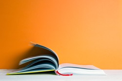 book on a white table, orange background