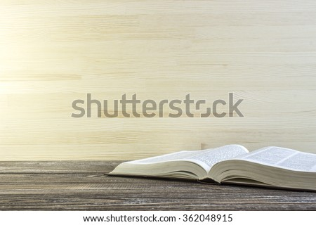 Book on a wooden table. Book is a dictionary. Toned