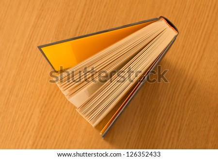 Book on wooden table viewed above