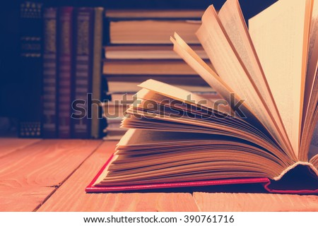 Book opened in library on wooden shelf. Education background with copy space for text. Toned photo