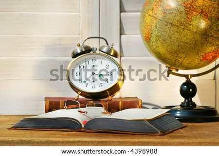 Book opened with clock on desk