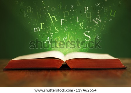 Book or bible on table with flying letters on green background - stock ...