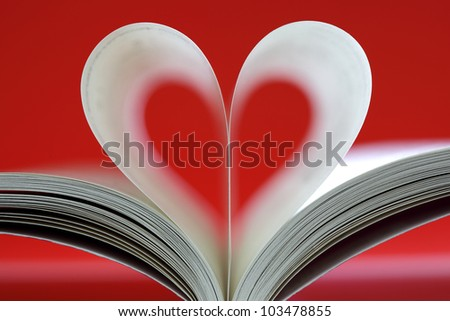 Book pages folded into heart shape on red background