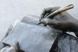 Book, pen and hands of a writer. Sculpture closeup