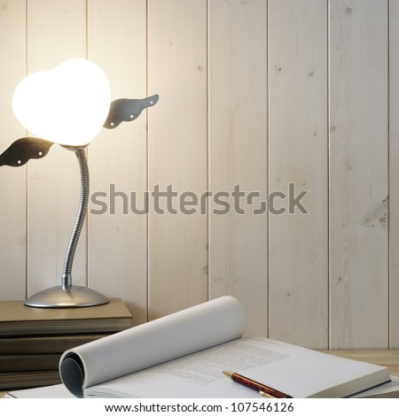 Book,pen and lamp on wooden desk