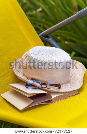 book, points and hat lie in a Beach Chair