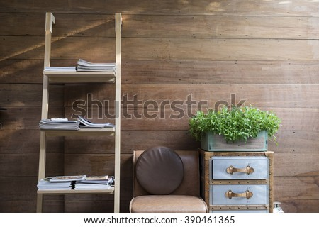 Book shelf ladder, leather chair, and vintage drawer with plant wooden vase on it with wooden wall background