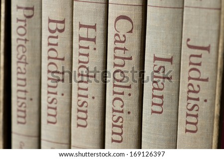 Shutterstock Book spines listing major world religions - Judaism, Islam, Catholicism, Hinduism, Buddhism and Protestantism. The focus is on the word, Catholicism.