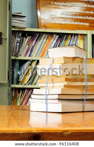 Book stack against book shelf in library