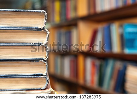 Book stack and book shelf in a library background