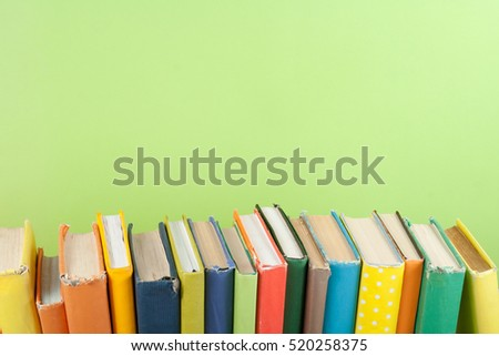 Book stack, hardback colorful books on wooden table and green background. Back to school. Copy space for text. Education concept.
