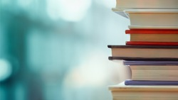 Book stack in the library room and blurred bookshelf for business and education background, back to school concept