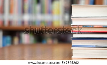 Book stack on wood desk and blurred bookshelf in the library room, education concept