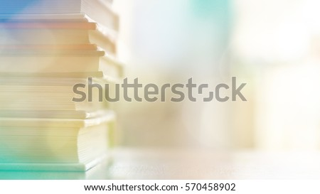 Book stack on wood desk in the library room and soft focus with bright light, education and business background