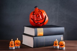Book stack with scary pumpkin candles, jack o lantern against grey stone background, copy space, Halloween still life