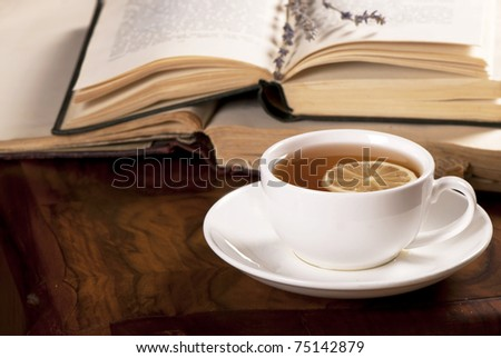 book, tea on wooden board