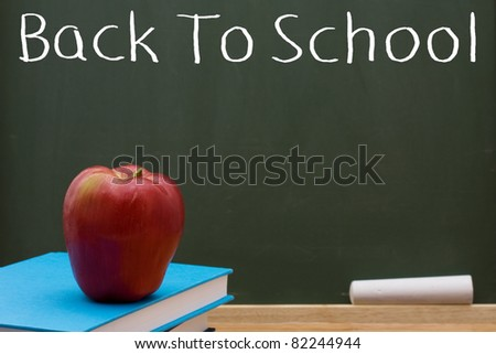 Book with an apple in front of a chalkboard, Back to School - stock photo