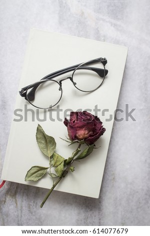 Book with beautiful  dried rose and glasses, from above - Shutterstock ID 614077679