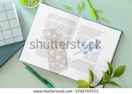 Book with bookmarks and stationery on color background Сток-фото ©