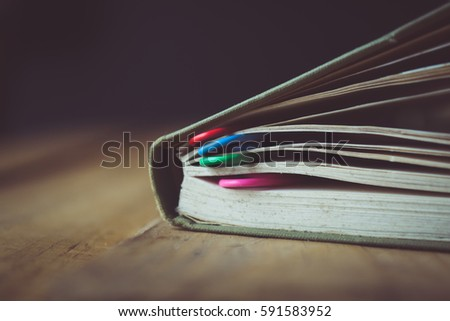 book with bookmarks of  colored paper clips