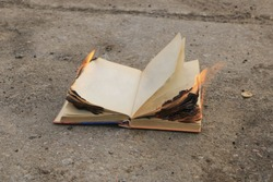 book with burning pages on a concrete surface