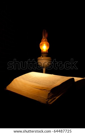 book with candle lamp on a black