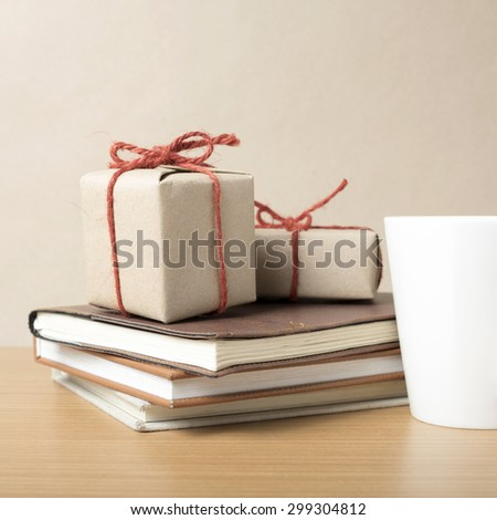 book with gift box and coffee mug on wood background