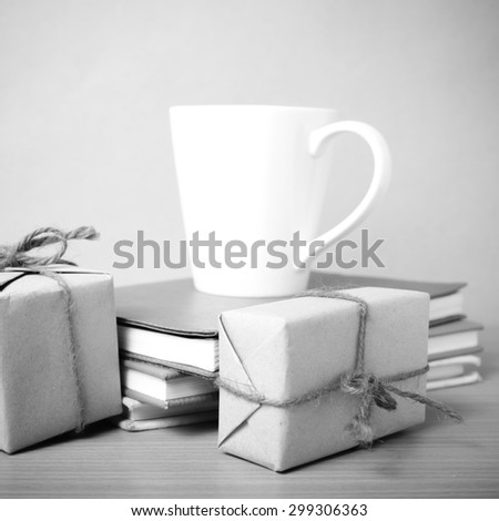 book with gift box and coffee mug on wood background black and white tone style