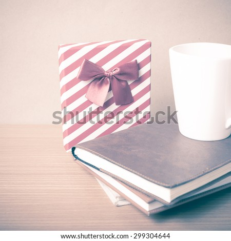 book with gift box and coffee mug on wood background vintage style