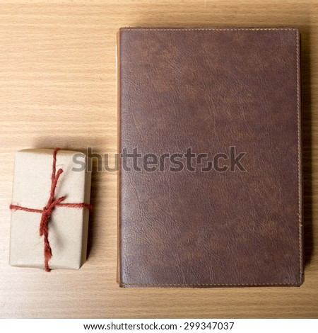 book with gift box on wood background