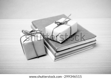 book with gift box on wood background black and white tone style