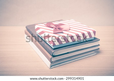 book with gift box on wood background vintage style