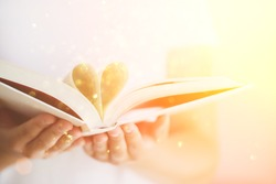 Book with opened pages and shape of heart in girl hands. Copy space. Love concept. Festive background with bokeh and sunlight