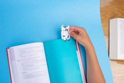 book with paper cow bookmarks , soft focus, kids hand holding paper cow, top view, holiday craft for children