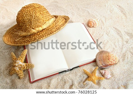 Book with straw hat and seashells at the beach